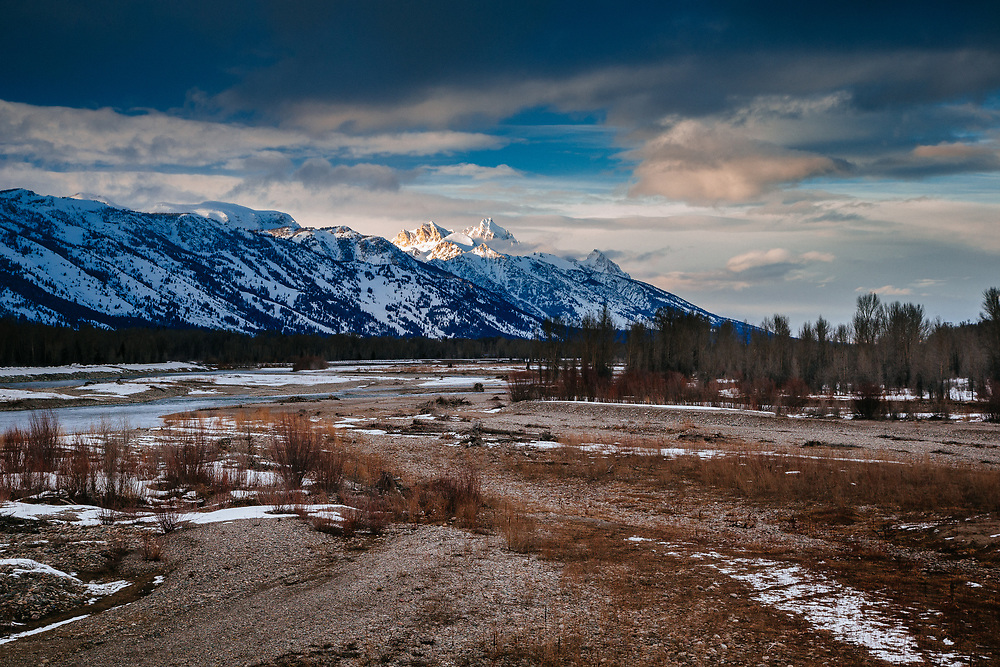 A winter storm clears at sunset giving views of Grand Teton above the valley along the Snake River near Wilson, Wyoming.