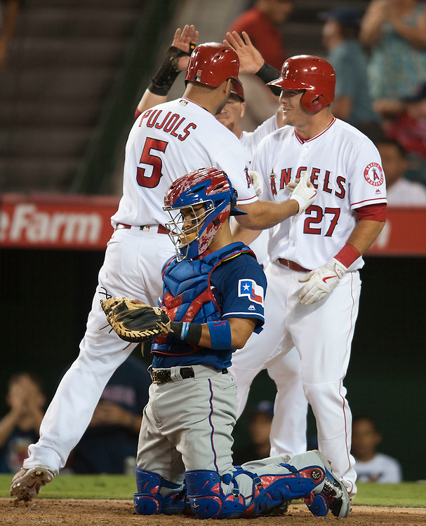 The Angels' Albert Pujols celebrates at home with Mike Trout and Kole Calhoun in front of Texas catcher Robinson Chirinos after his first three-run home run of the game in the fifth inning at Angel Stadium on Tuesday.<br /> <br /> ///ADDITIONAL INFO:   <br /> <br /> angels.0720.kjs  ---  Photo by KEVIN SULLIVAN / Orange County Register  -- 7/19/16<br /> <br /> The Los Angeles Angels take on the Texas Rangers at Angel Stadium.