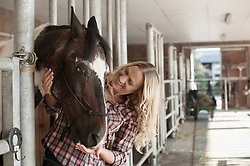 Mid adult woman stroking her horse in barn and smiling, Bavaria, Germany
