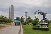 Dolphin statue in Miracle Park. Alphabetic tower and the old clock tower in the background. Batumi, Georgia