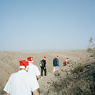 Gran Canaria, Spain. Norwegians walking in the mountains of Gran Canaria, heading for the annual Christmas service at La Plaza Noruega. La Plaza Noruega is a small, remote spot donated to the Norwegian community by the local authorities of Mogan. The red hats are mandatory on this day.<br /> Photo by Knut Egil Wang/Moment/INSTITUTE