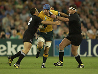Photo: Richard Lane.<br />New Zealand v Australia. Semi-Final, at the Telstra Stadium, Sydney. RWC 2003. 15/11/2003. <br />Nathan Sharp attacks as Aaron Mauger and Dave Hewett tackle.