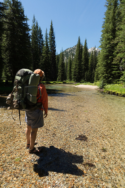 Backpacker crossing the West Fork of the Lostine River, Wallowa Mountains, Oregon.