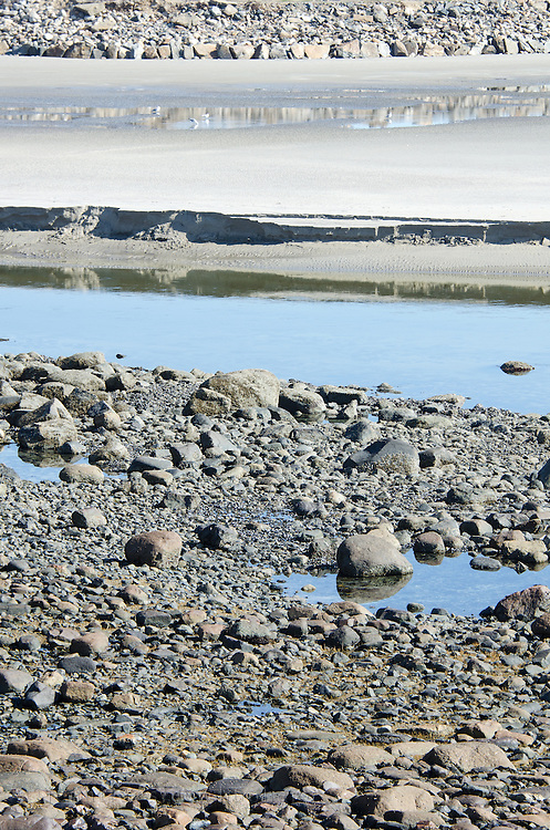 Low tide exposes layers of sand and stones on the beach at Ogunquit, Maine.