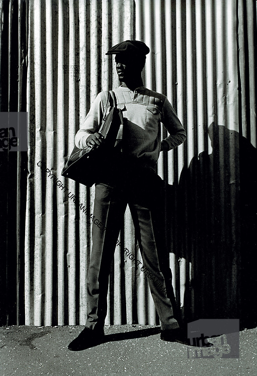 Waiting against a corrugated iron fence. Photo by Richard Saunders 1983