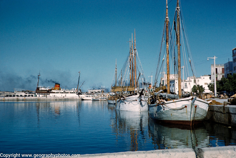 Traditional wooden sailing ships in harbour with funnel of ferry ship in background, San Antonio, island of Ibiza, Balearic Islands, Spain, 1950s