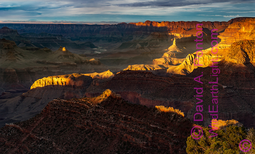Last sunlight catches a ridge and formations in the Grand Canyon, with the Colorado River visible in the distance. © David A. Ponton