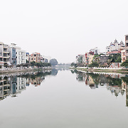 A channel in West Lake (Ho Tay) in Hanoi, Vietnam, with houses and apartments on either bank reflected on the calm waters.