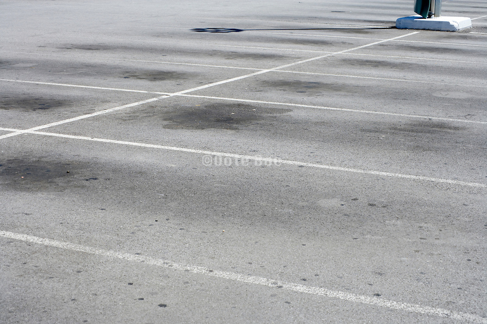 empty parking lot with oil spills on the asphalt