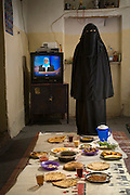 Saada Haidar, a housewife, with her typical day's worth of food at her home in the city of Sanaa, Yemen. (From the book What I Eat: Around the World in 80 Diets.) The caloric value of her day's worth of food in the month of April was 2700 kcals. She is 27 years of age; 4 feet, 11 inches tall; and 98 pounds. In public, Saada and most Yemeni women cover themselves for modesty, in accordance with tradition. MODEL RELEASED.