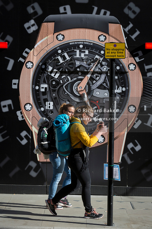 Two women walk past a construction hoarding of a watch outside the new Richard Mille shop in New Bond Street, on 25th February 2019, in London, England.