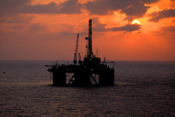 Stock photo of a semi-submersible rig on the ocean at sunset