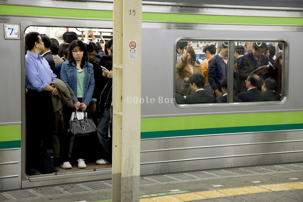 people waiting for the train to leave during evening rush Tokyo Japan