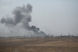 20/10/2016. Bashiqa, Iraq. Smoke from a coalition airstrike rises over the town of Tiskharab near Mosul, Iraq, during an operation to retake the Islamic State held town of Bashiqa today (20/10/2016).<br /> <br /> Launched in the early hours of today with support from coalition special forces and air strikes, the attack is part of the larger operation to retake Mosul from the Islamic State, and involves both the Kurds and the Iraqi Army. The city of Bashiqa, around 9 miles north of Mosul, is one of several gateway areas that must be taken before any attempted offensive on Mosul itself.<br /> <br /> Despite the peshmerga suffering several casualties after militants fought back using mortars, heavy machine guns and snipers, the Kurdish forces were quickly taking ground with Haider al-Abadi, the Iraqi prime minister, stating that the operation to retake Mosul was progressing faster than expected. Photo credit: Matt Cetti-Roberts/LNP