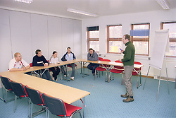 Group of youths in training room attending lifeskills session at day centre for homeless and vulnerably housed young people,