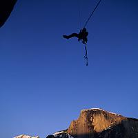 ROCK CLIMBING, Willie Benegas rappels on Washington Column, Yosemite, Half Dome bkg.
