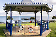 Seen through a modern bandstand that features characters from Alice in Wonderland, a couple sit facing out to see and Llandudno Pier, on 4th October 2021, in Llandudno, Gwynedd, Wales. Llandudno was the holiday destination resort of the Alice Liddell, the girl who inspired Lewis Carroll in his story Alice in Wonderland, and for whom Caroll based his worldwide famous story on. Alice Liddell used to visit Llandudno and stay in her holiday home Penmorfa, with her family.