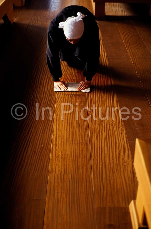 """A Zen monk of the Soto School cleans the meditation hall in the traditional manner at the Seiryu-ji Temple in Hikone City, Japan.Sitting Zen (or Zazen) is at the heart of Buddhist practice in Japan..In Zen Buddhism, zazen (literally """"seated meditation"""") is a meditative discipline practitioners perform to calm the body and the mind and experience insight into the nature of existence and thereby gain enlightenment (satori). 'Sammu' or work is a practice of 'moving Zen': a mindless repetition of activity that frees the mind."""