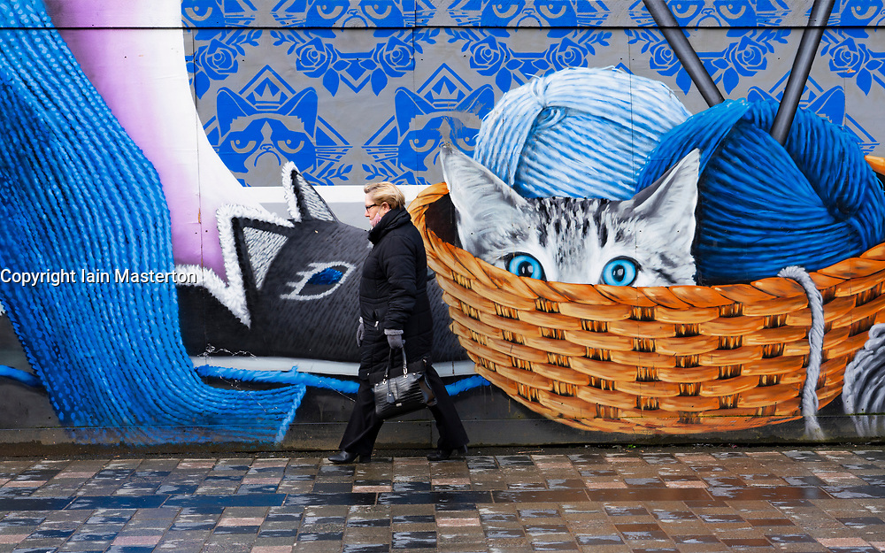 Glasgow, Scotland, UK. 12 March 2021. On the day Covid-19 lockdown is relaxed slightly in Scotland the city centre streets in Glasgow city centre remain almost deserted virtually all shops ad cafes are still closed. Pic; Member of public walks past striking mural on Sauchiehall Street.  Iain Masterton/Alamy Live News