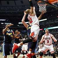 26 March 2012: Chicago Bulls forward Taj Gibson (22) goes for the dunk on Denver Nuggets center Timofey Mozgov (25) during the Denver Nuggets 108-91 victory over the Chicago Bulls at the United Center, Chicago, Illinois, USA. NOTE TO USER: User expressly acknowledges and agrees that, by downloading and or using this photograph, User is consenting to the terms and conditions of the Getty Images License Agreement. Mandatory Credit: 2012 NBAE (Photo by Chris Elise/NBAE via Getty Images)