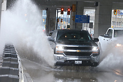April 16, 2018 - Toronto, ON, Canada - TORONTO, ON - APRIL 16:  -  Drivers drive through of pool of water from ongoing rainfall on Lakeshore Ave just south of the Rogers Centre. Vince Talotta/Toronto Star (Credit Image: © Vince Talotta/The Toronto Star via ZUMA Wire)