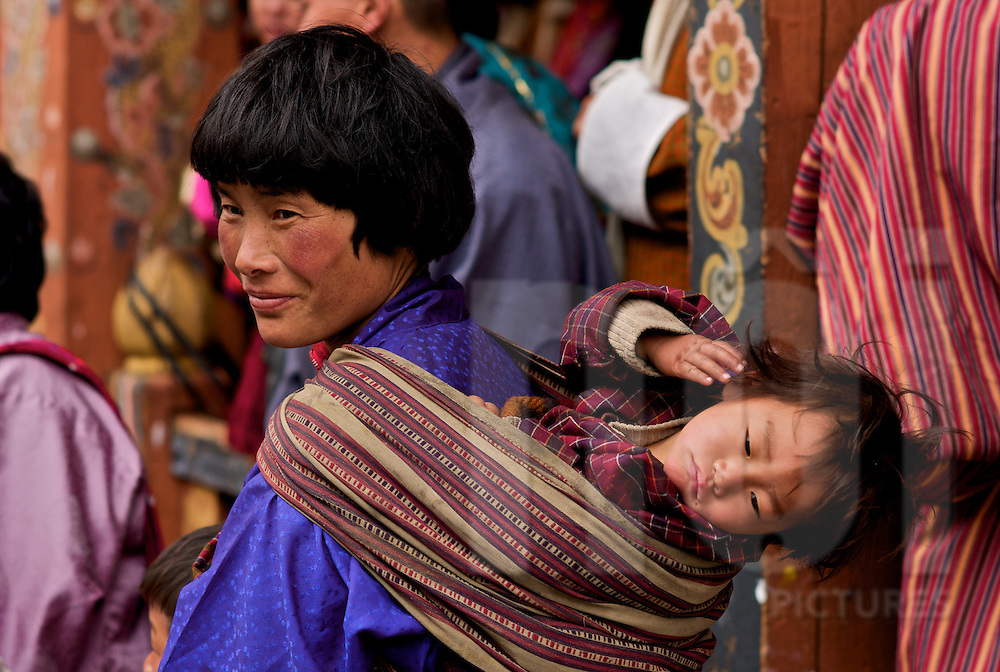 A Bhutanese mother carries her child on her back during the Trongsa Dzong Festival in Bhutan, Asia