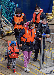 © Licensed to London News Pictures. 03/08/2021. Dover, UK. Migrants are helped ashore by Border Force officers at Dover Harbour in Kent after crossing the English Channel. Hundreds of migrants have made the crossing in recent weeks. Photo credit: Stuart Brock/LNP