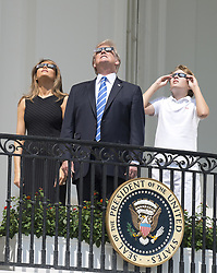 August 21, 2017 - Washington, District of Columbia, United States of America - United States President Donald J. Trump, center, accompanied by first lady Melania Trump, left, and Barron Trump, right, look at the partial eclipse of the sun from the Blue Room Balcony of the White House in Washington, DC on Monday, August 21, 2017..Credit: Ron Sachs / CNP (Credit Image: © Ron Sachs/CNP via ZUMA Wire)