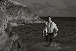 handsome muscular man with an open shirt walking in the ocean in Bermuda