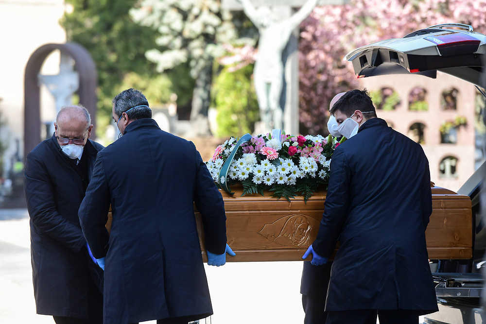 Bergamo, Italy - 16 March 2020: Men wearing face masks unload a coffin from a hearse at the Monumental Cemetery