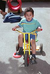 Nursery school boy riding tricycle around playground,