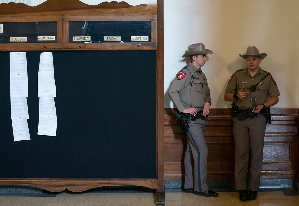 Texas Dept. of Public Safety (DPS) officers wait in the Texas House foyer while next weeks' calendar is posted on the board outside the chamber of July 8, 2021.