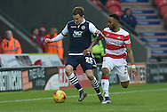 Jed Wallace of Millwall FC under attack from Cedric Evina  of Doncaster Rovers   during the Sky Bet League 1 match between Doncaster Rovers and Millwall at the Keepmoat Stadium, Doncaster, England on 27 February 2016. Photo by Ian Lyall.