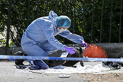 © Licensed to London News Pictures. 01/06/2019. London, UK. A forensic officer looking though the victims jacket on Seven Sisters Road, near the junction of Vartry Road in Haringey, north London, where a man in his 30s was found suffering from a stab wound to his leg. Police were called by London Ambulance Service just after 3am on Saturday, 1 June 2019. The victims condition in unknown.  Photo credit: Dinendra Haria/LNP