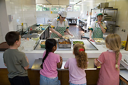 Children standing at counter in school canteen waiting for food,