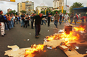 Debris burns in the Chacao section of Caracas along Altamira Square where opposition members are protest the results of the presidential recall referendum that leaves Venezuela's president Hugo Chavez in power, Monday, August 16, 2004. Hours earlier, a woman was killed and several injured when alleged Chavistas open fire on a crowd of Opposition protesters in Altamira square.  Photographer: Emile Wamsteker/World Picture News
