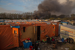 "Calais, Pas-de-Calais, France - 26.10.2016    <br />  <br /> Since the beginning of the governmental camp destruction on the day before many fires were placed by camp residents inside camp. Wide parts of the camp burned down. 3rd day of the eviction on the so called îJungle"" refugee camp on the outskirts of the French city of Calais. Many thousands of migrants and refugees are waiting in some cases for years in the port city in the hope of being able to cross the English Channel to Britain. French authorities announced a week ago that they will evict the camp where currently up to up to 10,000 people live.<br /> <br /> Seit dem Beginn der behoerdlichen Campzerstˆrung wurden zahlreiche Feuer im Camp gelegt. Weite Teile des Camps brannten ab. Dritter Tag der Raeumung des so genannte îJungleî-Fluechtlingscamp in der franzˆsischen Hafenstadt Calais. Viele tausend Migranten und Fluechtlinge harren teilweise seit Jahren in der Hafenstadt aus in der Hoffnung den Aermelkanal nach Groflbritannien ueberqueren zu koennen. Die franzoesischen Behoerden kuendigten vor einigen Wochen an, dass sie das Camp, indem derzeit bis zu bis zu 10.000 Menschen leben raeumen werden. <br /> <br /> <br /> / 261016"