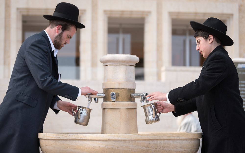 19 April 2019, Jerusalem: Two men wash their hands, as on the first day of Pesach (Passover) Jews gather to pray by the Western Wall in Jerusalem, considered as the most sacred and holy place for the Jews.