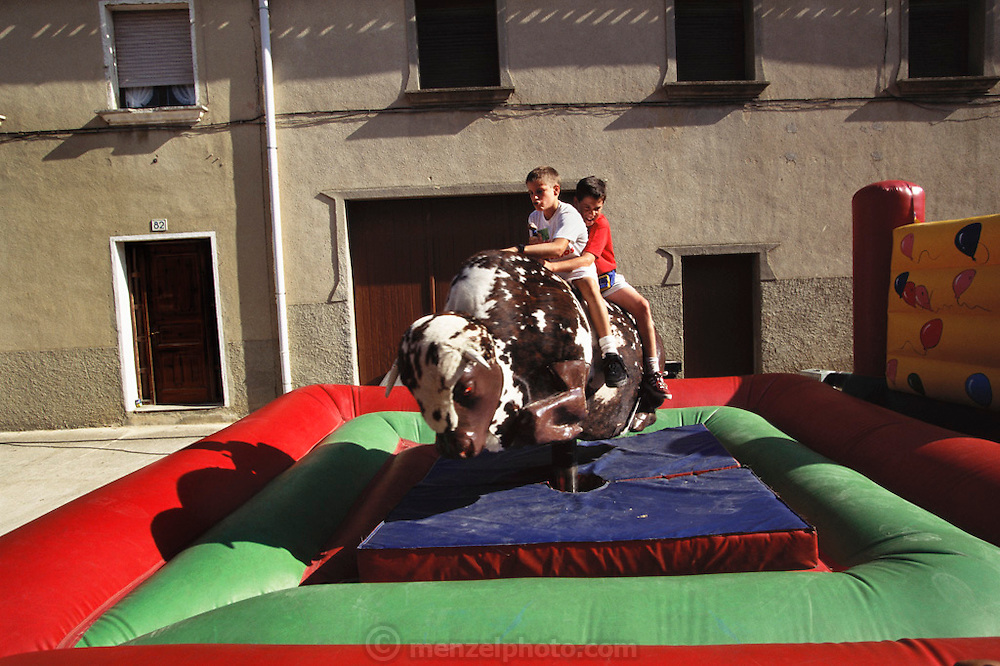 A bucking mechanical bull is ridden between live traditional bull running in the town of Artajona which is celebrating its feast day with the usual week of festivities. Navarra, Spain.