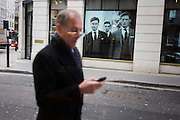 A man walks past menswear clothing shop while apparently messaging with a mobile phone handset in city of London.