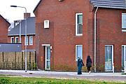 Nederland, Arnhem, 25-4-2017In de wijk Malburgen in Arnhem Zuid worden veel huurhuizen vervangen door nieuwbouw. De oude sociale woningen stammen uit de vijftiger en zestiger jaren en zijn aan vervanging toe. Twee allochtone vrouwen met een migrantenachtergrond, migratieachtergrond wandelen op de stoep, hun hoofd bedekt met een hoofddoek. Het zijn moslims.Foto: Flip Franssen
