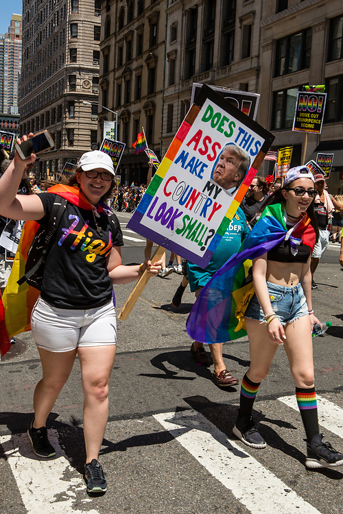 """New York, NY - 25 June 2017. New York City Heritage of Pride March filled Fifth Avenue for hours with groups from the LGBT community and it's supporters. A woman with a sign bearing a photo of Donald Trump, and which reads """"Does this ass make my country look small?"""""""