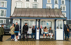 © Licensed to London News Pictures. 29/07/2018. Aberystwyth, UK. People shelter form the wet and overcast conditions at the seaside in Aberystwyth on the west Wales coast, as the long heatwave finally breaks down with thunderstorms and torrential rain over much of the country. photo credit:  Keith Morris/LNP