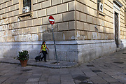A woman wheels her shopping trolley through the Piazza Bellini, Palermo, Italy