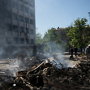 Locals pass by burning debris in front of local government building in Mariupol, hours after deadly clashes between separatists armed groups and the Ukrainian Army over the control of key buildings in the city.