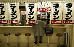 Man eating at traditional snack bar in an Osaka railway station