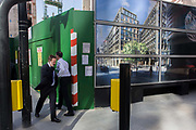 Two businessmen pass close to each other, next to a construction hoarding for a future office building. The location is on the corner of Walbrook and Cannon Street in the capital's financial heart - the City of London, known as the Square Mile, founded by the Romans in AD43. Here, the construction site behind the screen, is where archeologists have discovered rare finds from the early Centuries AD. Nowadays, a new office block is being constructed as shown on the hoarding's  illustration.