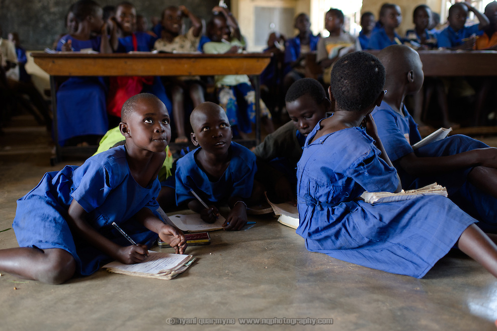 As the school is short of desks, some students sit o the floor at Aputiri Primary School in Eastern Uganda on 31 July 2014. The school participates in a Menstrual Health Management program supported by Plan International, which is aimed at both boys and girls.