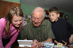 Grandfather and grandchildren playing on Nintendo DS game UK