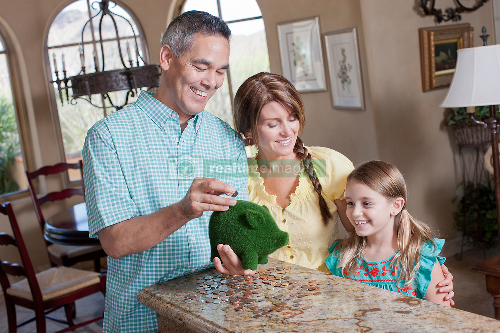 Family saving money in green piggy bank (Credit Image: © Image Source/Dan Bannister/Image Source/ZUMAPRESS.com)